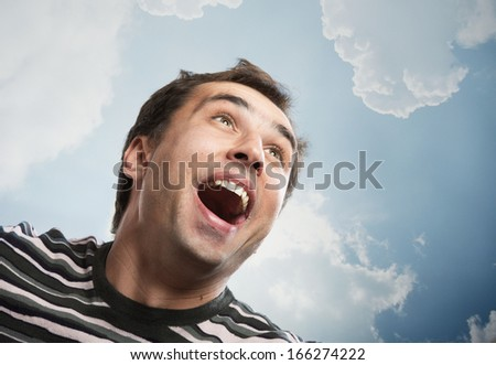 Portrait of a joyful man looking up against a sky background - stock photo