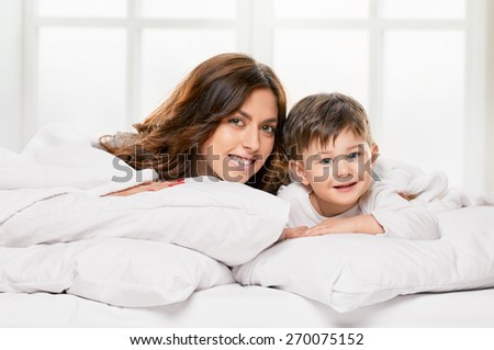 Portrait of a joyful mother and her baby son in the bed on light window background - stock photo
