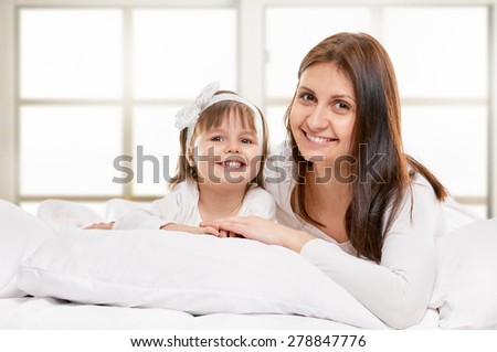 Portrait of a joyful mother and her daughter in the bed on light window background - stock photo