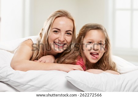Portrait of a joyful mother and her daughter in the bed on window background - stock photo