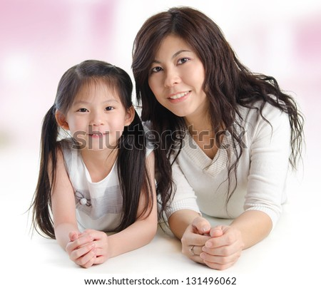 Portrait of a joyful mother and her daughter smiling at the camera. Happy Asian family lying at home. - stock photo