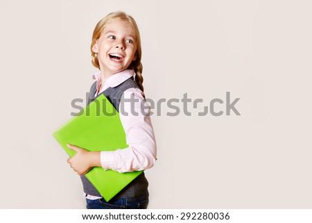 Portrait of a joyful schoolgirl with a book. School and education - stock photo