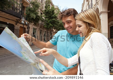 Portrait of a joyful tourist young couple relaxing sightseeing and visiting a destination city on holiday, reading a map and enjoying traveling together, outdoors. Tourism, travel and lifestyle. - stock photo
