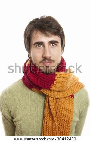 Portrait of a joyful young man wearing a scarf and green pullover against white background - stock photo