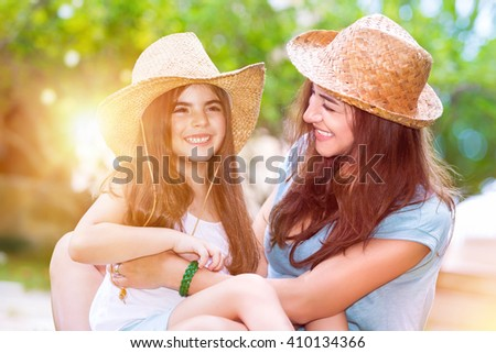 Portrait of a joyful young mother with a cute cheerful daughter wearing same straw hats and playing outdoors, laughing and having fun, portrait of a happy family enjoying life - stock photo