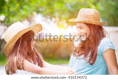 Portrait of a joyful young mother with her cute cheerful daughter wearing same straw hats and playing outdoors, laughing and looking on each other, portrait of a happy family enjoying life - stock photo