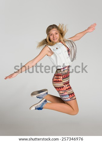 Portrait of a jumping girl on the gray background - stock photo