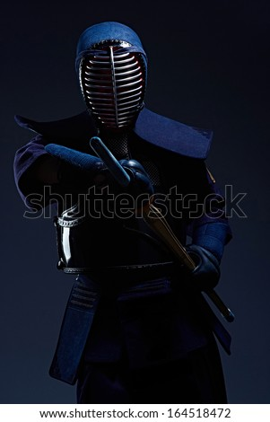 portrait of a kendo fighter with shinai, dark background - stock photo