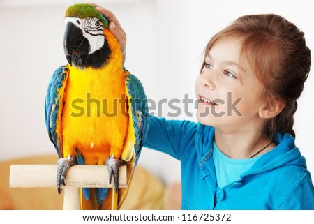 Portrait of a kid girl with her domestic ara parrot - stock photo