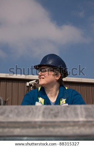 Portrait of a lady construction worker wearing a hard hat with blue sky as background - stock photo