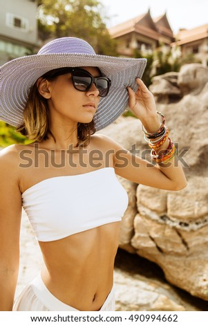 Portrait of a lady in white skirt, top, sunglasses and summer straw hat in front of resort on rocks. Beauty cute girl on a tropical beach sea ocean shore with large stones. Outdoor summer lifestyle.