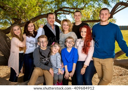 Portrait of a large family at the park, under a tree.  Parents with their eight children.  Three brothers and fours sisters makes for lots of siblings. - stock photo