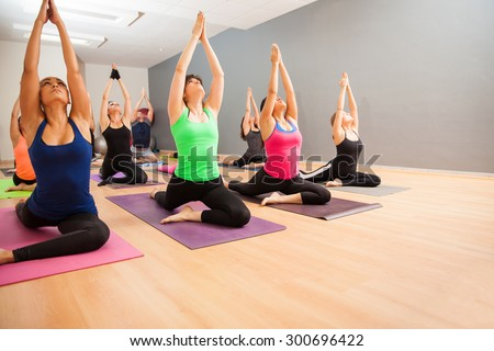 Portrait of a large group of people doing a low lunge pose during a real yoga class - stock photo