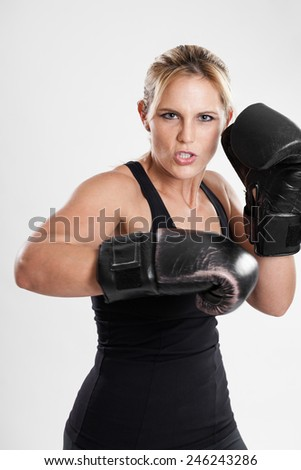 Portrait of a late 20s beautiful woman boxer throwing punches on a white background - stock photo