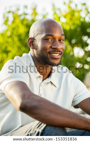 Portrait of a late 20s handsome black man sitting outside at a park in summer