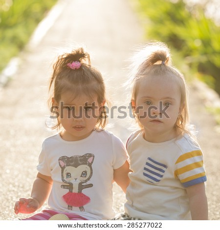 portrait of a laughing girl with Down syndrome and girlfriends - stock photo