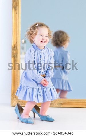 Portrait of a laughing toddler girl with beautiful curly hair wearing a blue dress is trying on her mother's elegant high heels shoes standing in front of a big mirror in a white bedroom  - stock photo