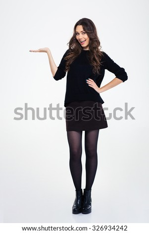 Portrait of a laughing woman holding copypace on the palm isolated on a white background - stock photo
