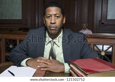 Portrait of a lawyer sitting with books and documents and woman in the background - stock photo