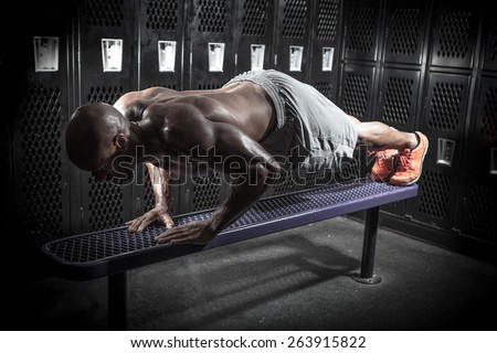 Portrait of a lean toned and ripped muscle fitness man doing push ups on a locker room bench under dramatic low key lighting.