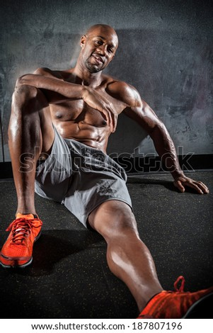 Portrait of a lean toned and ripped muscle fitness man under dramatic low key lighting. - stock photo
