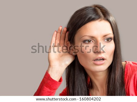 Portrait of a listening young woman on gray background - stock photo