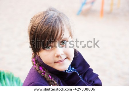 portrait of a littl girl  with pigtails  outdoors