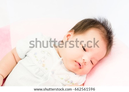 Portrait of a little adorable infant baby girl lying on back on the pillow