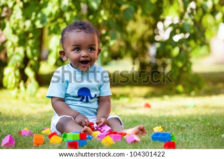 Portrait of a little african american baby boy playing outdoor in the grass - stock photo