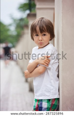 Portrait of a little angry boy, outdoors, boy expressing his emotions - stock photo