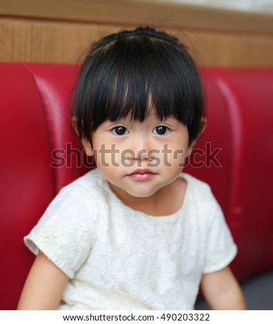 Portrait of a little Asian baby child girl on red sofa