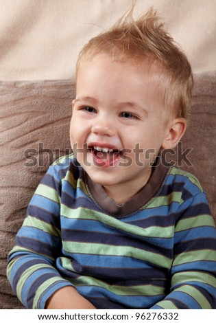Portrait of a little baby boy laughing outloud. Indoor shot. - stock photo