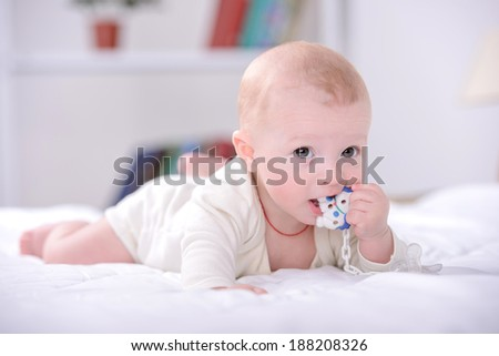 Portrait of a little baby playing on bed - stock photo