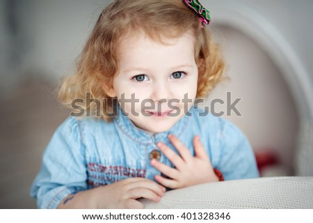 Portrait of a little blonde curly-haired girl in denim dress. - stock photo