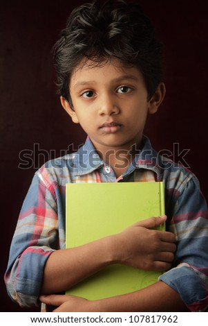 Portrait of a little boy holding a book