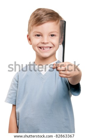 Portrait of a little boy holding a comb over white background