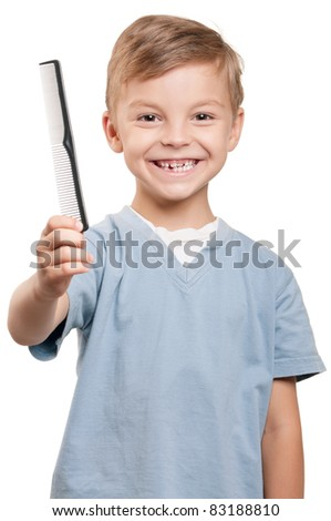 Portrait of a little boy holding a comb over white background - stock photo
