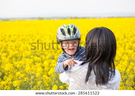 Portrait of a little boy in a helmet in an embrace with his mother. - stock photo