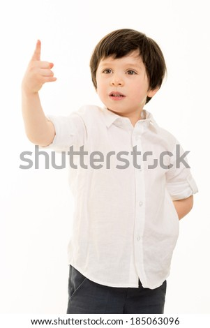 Portrait of a little boy in a white shirt pointing upwards against a white background