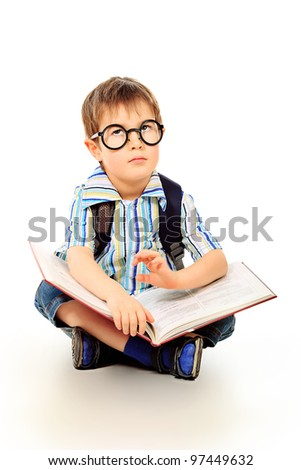 Portrait of a little boy in spectacles reading a book. Isolated over white background.
