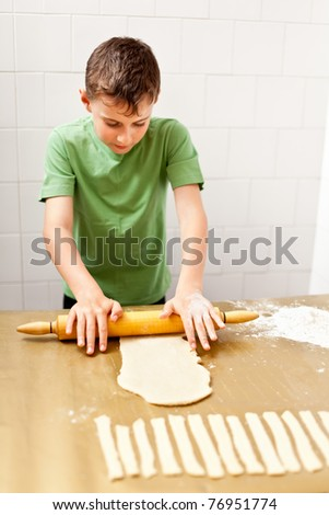 Portrait of a little boy in the kitchen using rolling pin to prepare the dough for cookies