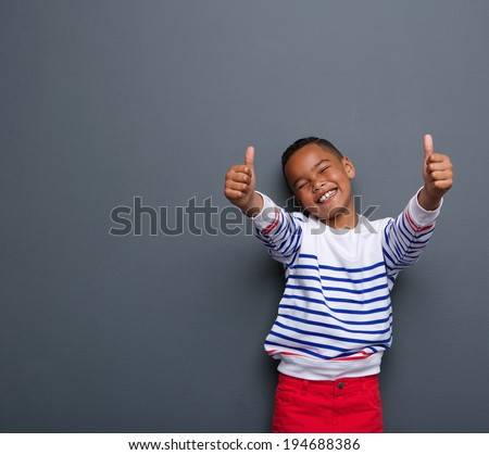 Portrait of a little boy laughing with thumbs up sign on gray background - stock photo