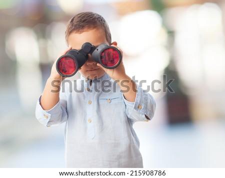 portrait of a little boy looking through the binoculars - stock photo