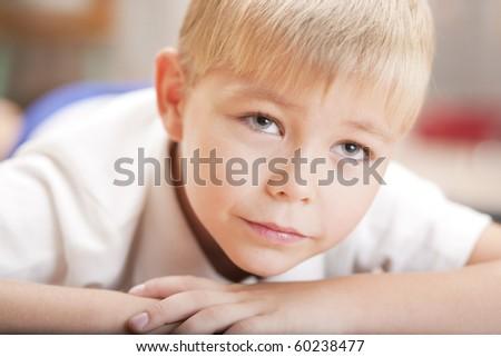 Portrait of a little boy lying on the floor - stock photo