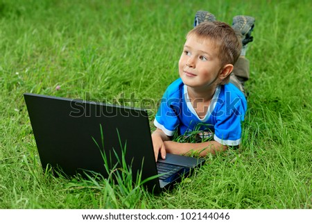 Portrait of a little boy lying with his laptop on a grass at a park. - stock photo