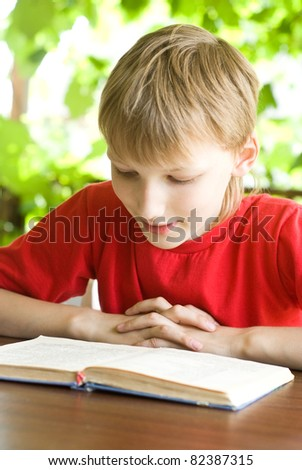 portrait of a little boy reading a book