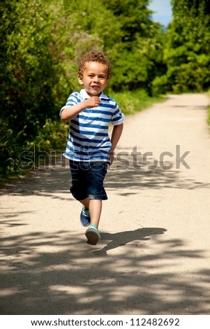 Portrait of a little boy running and having fun on a sunny day - stock photo