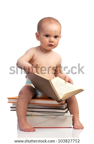 Portrait of a little boy sitting on a stack of books - stock photo