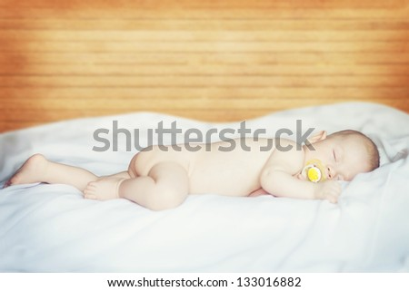 portrait of a little boy sleeping with a pacifier - stock photo