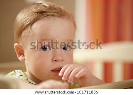 Portrait of a little boy staying in playpen and looking to the camera with eyes full of fear. Nice warm colors, shallow dof. - stock photo